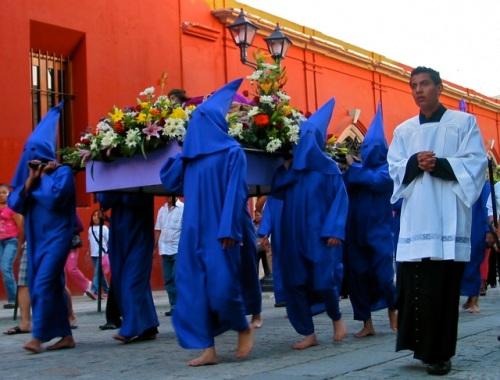 Purple hooded men carry a Jesus statue