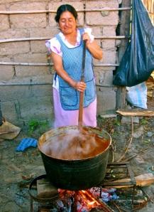 Woman stirring cauldron of mole.