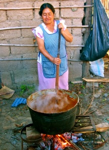 Woman stirring cauldron of mole.