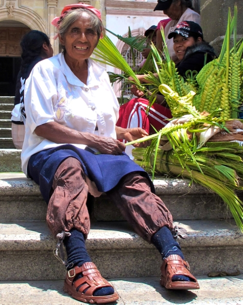 Palm frond weaver on stairs.