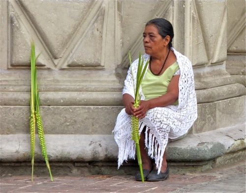 Woman seated on stoop with palm fronds.