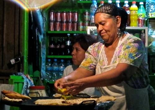 Vendor making empanadas, memelas, tortas, and tlayudas on a comal.