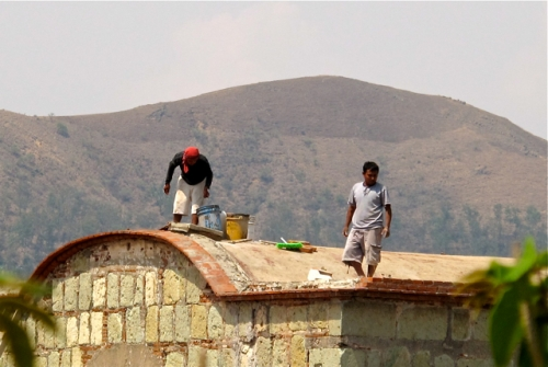 2 men replacing brickwork on roof of School of Fine Arts, Oaxaca.