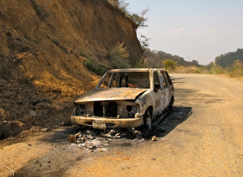 Burned out car on mountain road