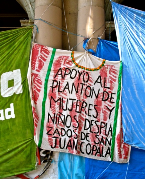 Banner in the style of a huipil with text:  Apoyo al planton de mujeres y niños desplazados de San Juan Copala.