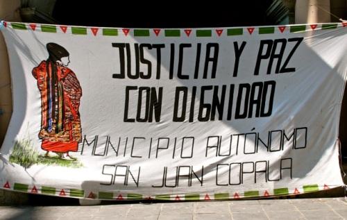 Banner - Triqui woman with slogan: Justicia y paz con dignidad; Municipio Autónomo San Juan Copala