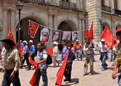 Demonstration by the Partido de los Comunistas Mexicanos with red flags and posters of Karl Marx, Frederick Engels, Vladimir Lenin, and Josef Stalin.
