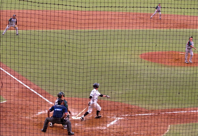 Guerreros baseball player at bat; fielder poised to catch ball seen through backstop netting.