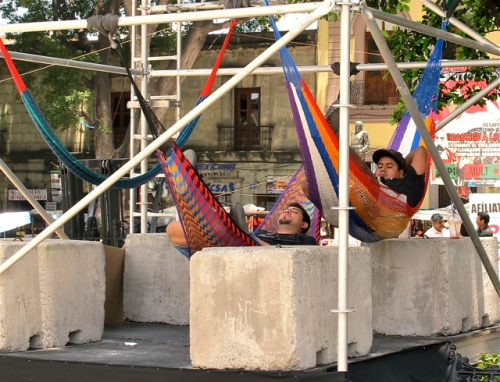 Two guys in hammocks hanging from stage scaffolding