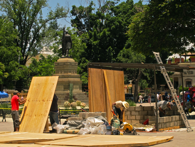 Carpenters building a booth in Llano Park next to statue of Benito Juárez