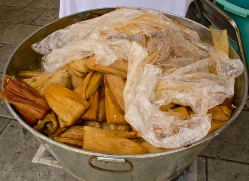 A variety of tamales in a metal bucket