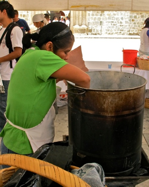 Woman reaching into steaming hot cauldron of tamales