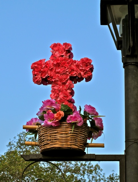 Cross of flowers extending from a lamp post