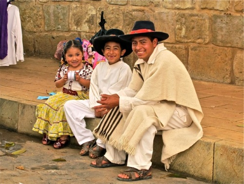 Father, daughter, and son dancers sitting on sidewalk waiting to perform