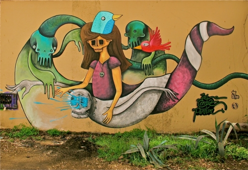 Colorful street art on wall with female skeleton, bird, and serpent