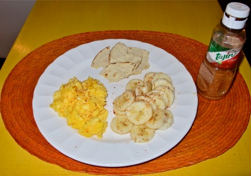 Plate with scrambled eggs and bananas sprinkled with Tajin and bottle of Tajin seasoning