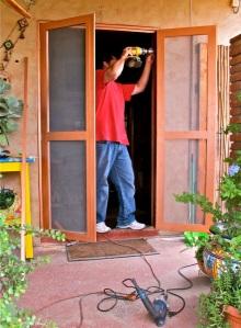 Juan, with drill, installing the new screen door
