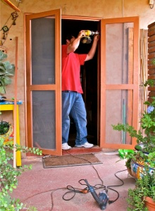 Juan, with drill, installing the new screen door