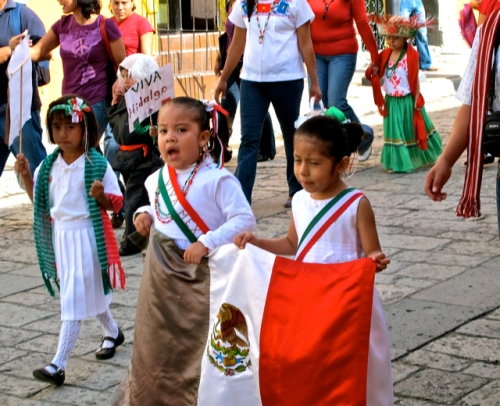 Children carrying Mexican flag and Viva Hidalgo sign.