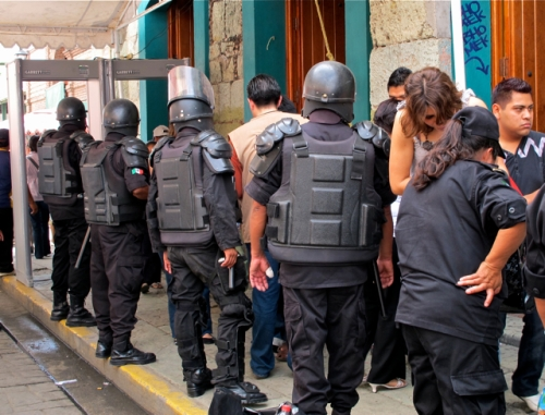 Black clad military with automatic weapons, wearing flak jackets and helmets, at security checkpoint