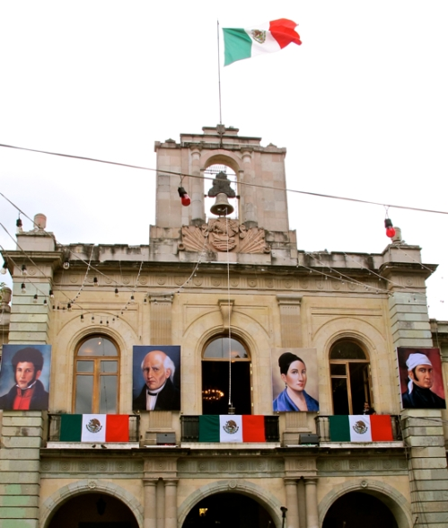 Government Palace with flags and color portraits of Mexican heroes of Independence.