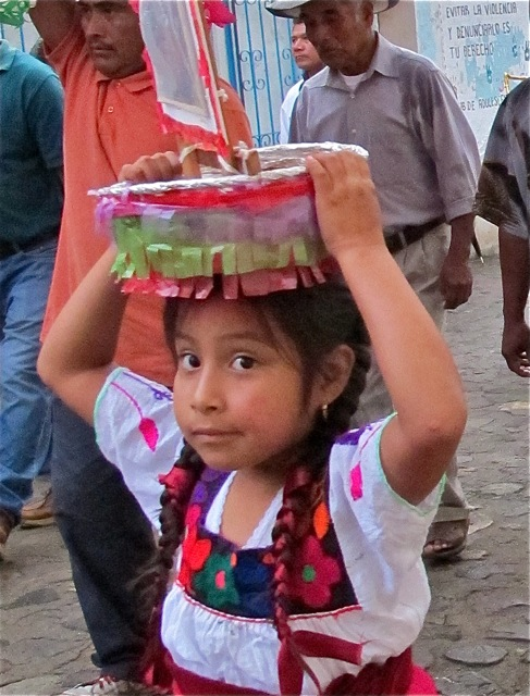 Young Zapotec girl carrying canasta on her head