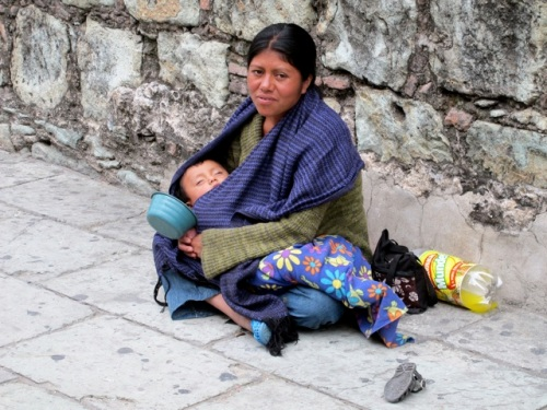 Mother seated on sidewalk, holding child, begging.