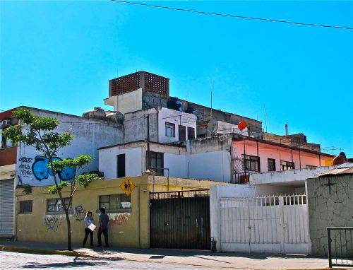 Concrete boxy buildings against clear blue sky.