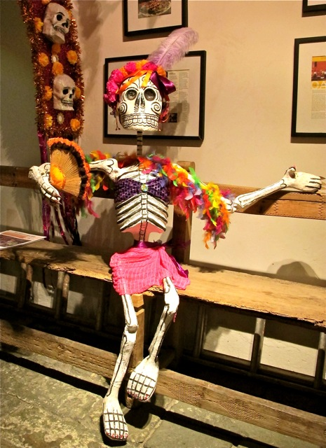 Skeleton in pink skirt and feather boa seated on a bench