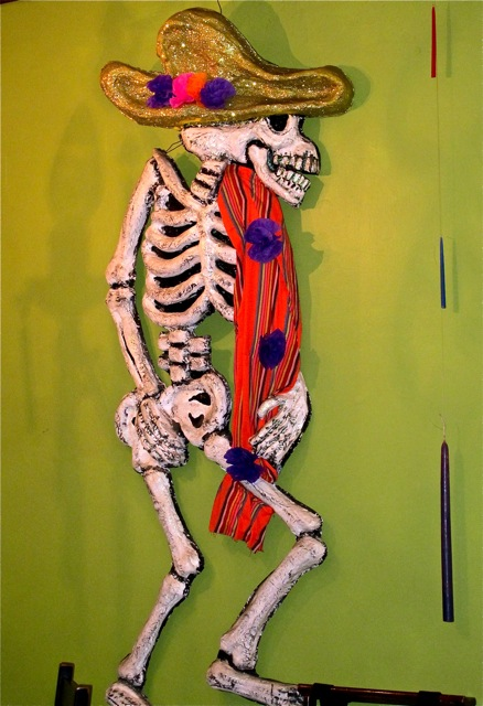 Skeleton with sombrero hanging on wall.