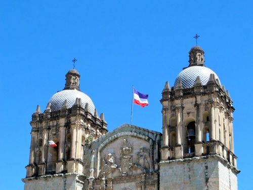 Purple, white, and red flag flying atop Santo Domingo