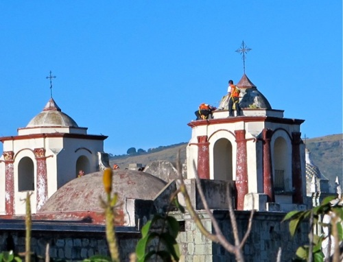 Workmen atop a cupola of Iglesia de San José against blue sky.