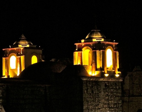 Lighted cupolas of Iglesia de San José against black night sky.