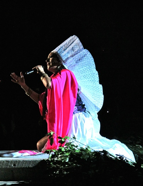Lila Downs kneeling, wearing traditional Tehuantepec headdress