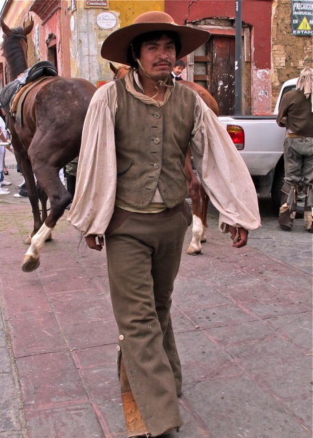 Independence fighter walking towards camera, horse in background