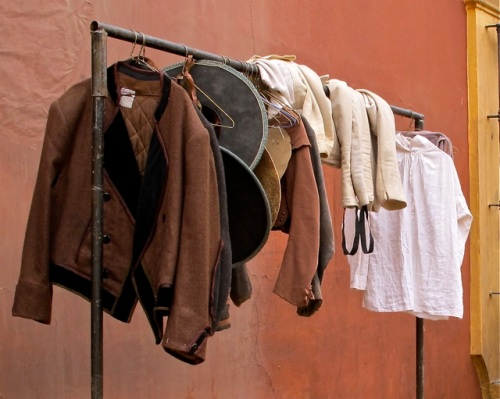Men's costumes hanging on rolling rack.