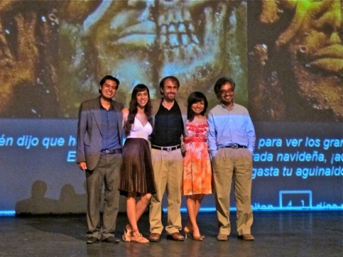 4 cast members and writer/director/producer standing in front of a projection of the home page of the website.
