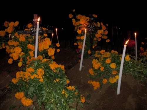 Marigolds and tall candles grave