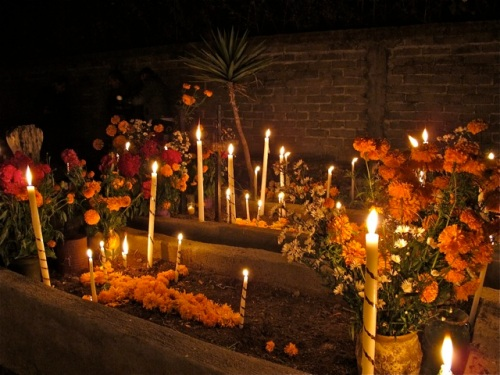 Tall candles and flowers in cemetary