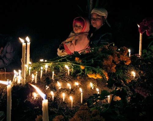 Mother holding child, illuminated by candles