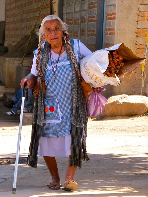 Elderly woman walking with cane and carrying a bundle of flowers