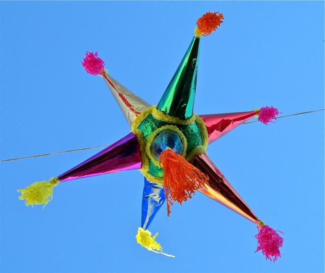 Multicolor star-shaped piñata against blue sky.
