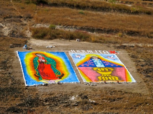 Sand paintings of the Virgin of Guadalupe and the Virgin of Juquila on a mountainside.