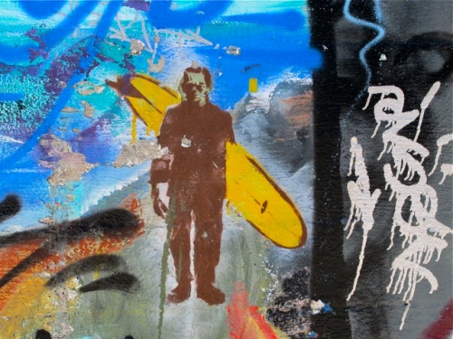 Wall art of surfer in wetsuit carrying surfboard