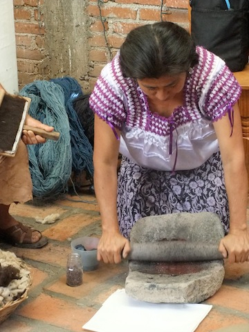 Woman grinding masa on stone matate