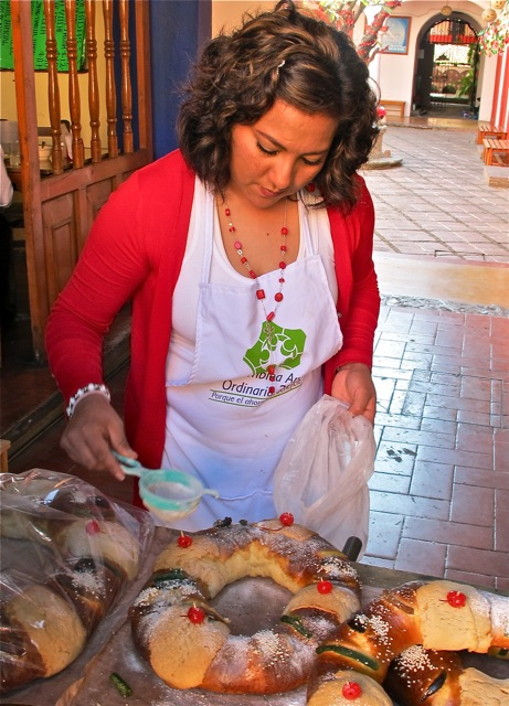 Woman putting powdered sugar on top of a Rosca de Reyes