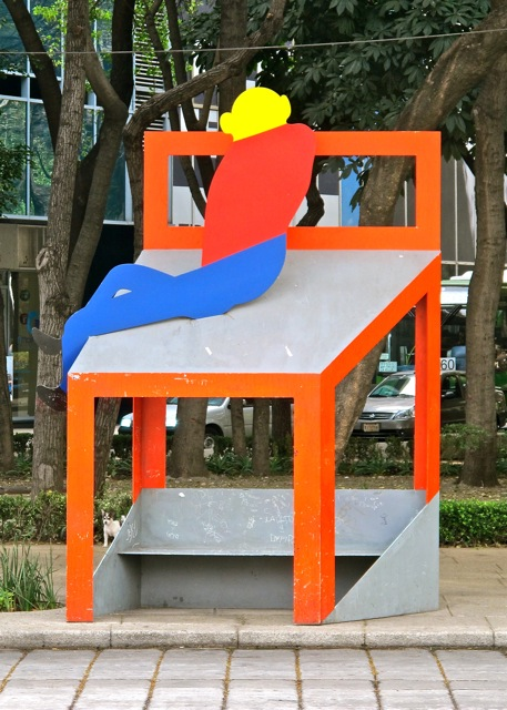 Aluminum bench topped with a whimsical red chair with lounging figure.