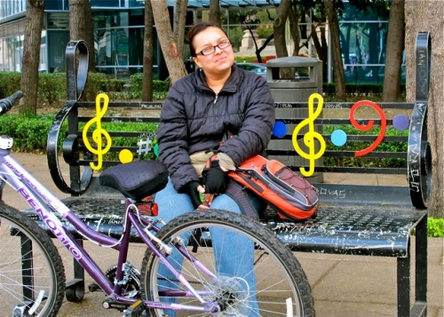 Smiling young woman sitting on a black iron bench with musical notations; her lavender bike in front.