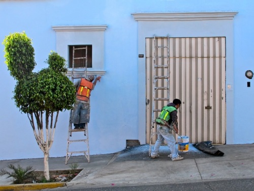 2 painters painting a pale blue building