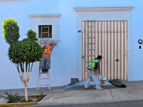 2 painters painting a pale blue building